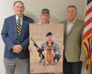 Paul Davis, state council president, Vietnam Veterans of America; Ken Bodine, chairman of the Memorial Committee; and Joe Startt Jr., president, Chapter 850, display the photo of SSGT Jason Spangenberg and his War Dog Rico. Group photo by Dave Skocik.